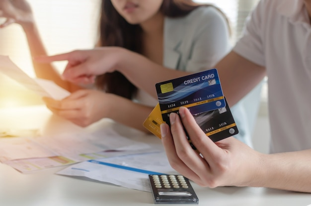 Uitgaven. jonge paar creditcard bedrijf en bezorgd over gezinsbudget onkosten rekeningen en rekenmachine op bureau in kantoor aan huis