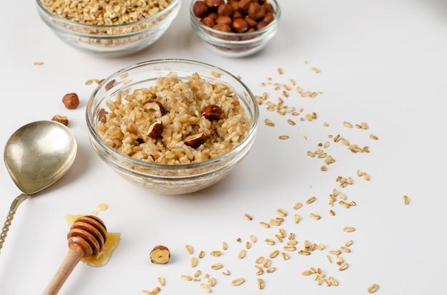 Uitgebalanceerd dieet-foodmenu voor ontbijt met havermoutpapkom met hazelnoten en honing