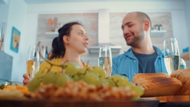 Uitgebreide familie roosteren met witte wijnglazen tijdens het diner, weekendviering. meerdere generaties, vier mensen, twee gelukkige koppels die praten en eten tijdens een gastronomische maaltijd, genietend van de tijd thuis.