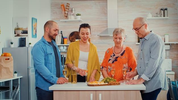 Uitgebreide gelukkige familie rammelende en blij om elkaar te zien. mensen van twee generaties praten, zitten rond de tafel te proosten en vieren een evenement met een glas witte wijn.
