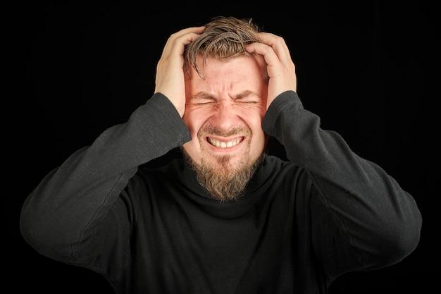 Uitgeput bebaarde man portret met hoofdpijn, zwarte achtergrond. overwerk, hoofdpijn concept. jonge kerel in zwarte polohals trui. uitgeput en moe om boos te worden man.