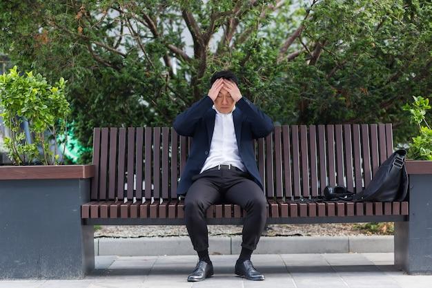 Uitgeput jonge aziatische zakenman kantoormedewerker zittend op een bankje in het stadspark buiten. beklemtoonde overwerkte man met hoofdpijn masseert hoofd. depressief vermoeide werknemer met pijn ziek werk
