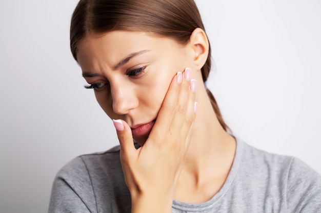 Uitgeput jonge vrouw die lijdt aan ernstige kiespijn
