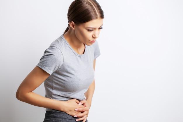 Uitgeput jonge vrouw die lijdt aan hevige buikpijn