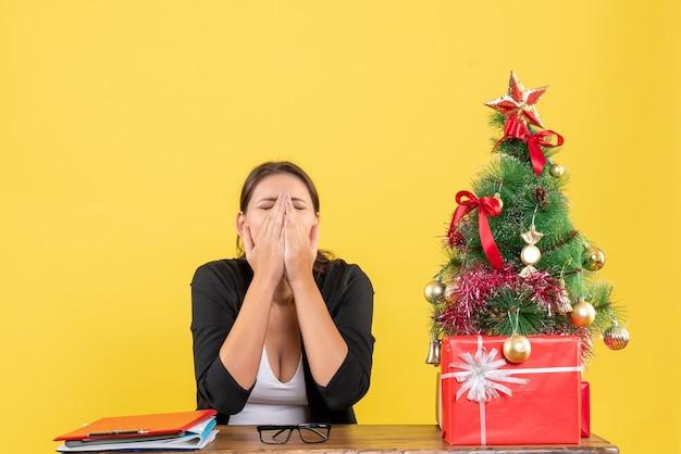 Uitgeput jonge vrouw in pak in de buurt van versierde kerstboom op kantoor op geel