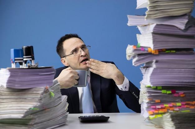 Uitgeput kantoormedewerker gaapt moe van het kijken naar enorme stapel documenten