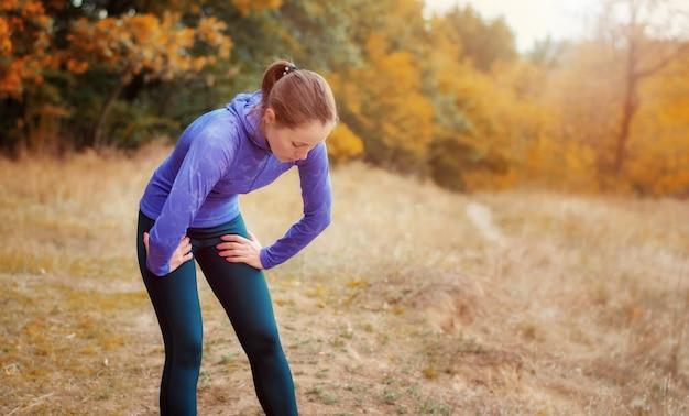 Uitgeput kaukasisch jogger-meisje in blauw overhemd en zwarte sportenleggings die na het joggen rusten