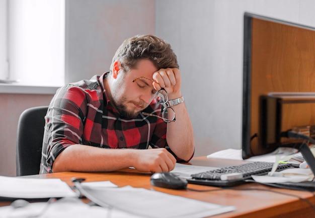 Uitgeput man aan het werk in een kantoor voor de deadline. close-up foto