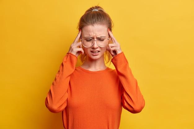 Uitgeput meisje raakt tempels, lijdt aan ondraaglijke hoofdpijn, fronst, draagt grote optische bril, oranje trui, staat binnen