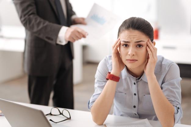 Uitgeput meisje zit op haar werkplek, leunend met haar hoofd op de handen die de lippen indrukt terwijl ze naar de voorkant kijkt