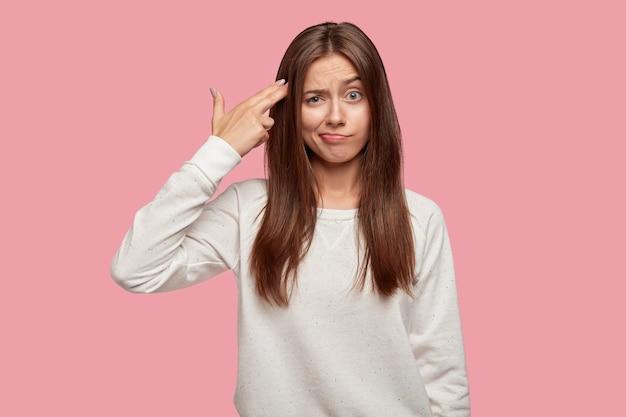Uitgeput mooie brunette poseren tegen de roze muur