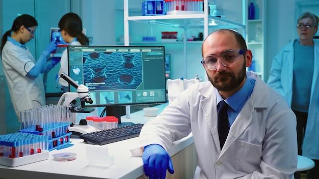 Uitgeput portret van scheikundige arts die naar de videocamera kijkt die in een uitgerust laboratorium zit en 's avonds laat werkt