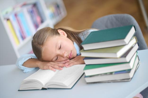 Uitgeput schoolkind liggend met haar ogen dicht op het bureau met boeken in een openbare bibliotheek