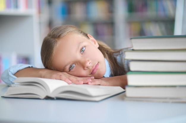 Uitgeput schoolkind liggend op haar bibliotheekboek