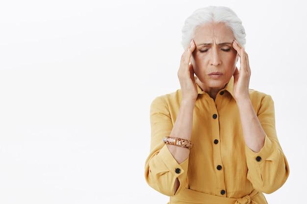 Uitgeput senior vrouw raakt haar hoofd aan, klaagt over migraine, heeft hoofdpijn