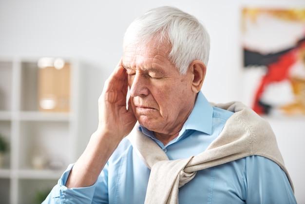 Uitgeput senior witharige man met gesloten ogen tempel aanraken terwijl hij hoofdpijn voelt