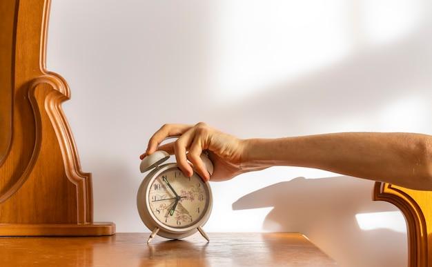 Uitgeput slaperig persoon zet de witte wekker 's ochtends uit b