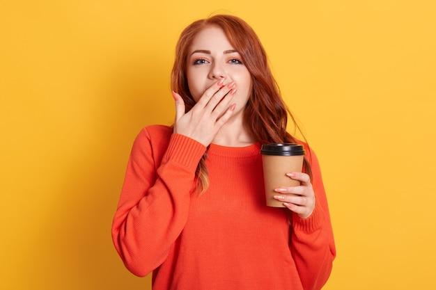 Uitgeput slaperig vrouwtje heeft een slapeloze nacht van examenvoorbereiding, gaapt en bedekt de mond met palmdrankjes afhaalkoffie om zich verfrist te voelen