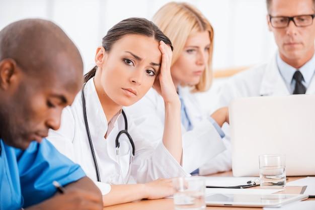 Uitgeput voelen. depressieve jonge vrouwelijke arts die de hand in het haar houdt terwijl ze samen met haar collega's op de vergadering zit