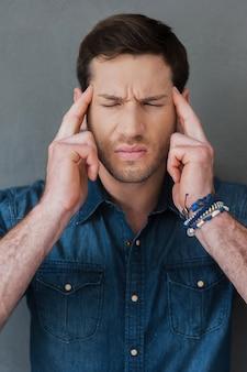 Uitgeput voelen. gefrustreerde jonge man die zijn hoofd aanraakt terwijl hij tegen een grijze achtergrond staat