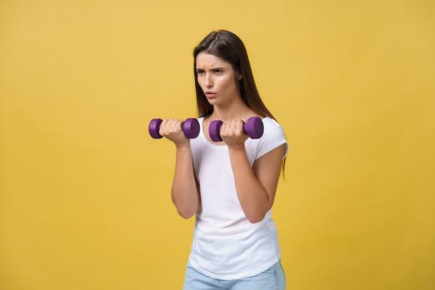 Uitgeput voelen. gefrustreerde jonge vrouw in wit overhemd oefenen met halters en serieuze blik terwijl staande geïsoleerd op gele achtergrond.