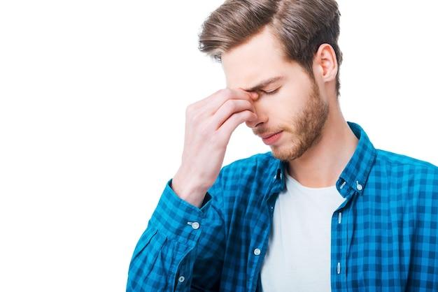 Uitgeput voelen. gefrustreerde jongeman die zijn neus masseert en zijn ogen gesloten houdt