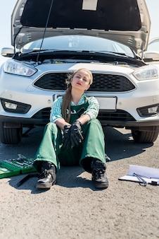 Uitgeput vrouw monteur met kapotte auto langs de weg