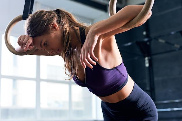 Uitgeput vrouw op gymnastiek ringen