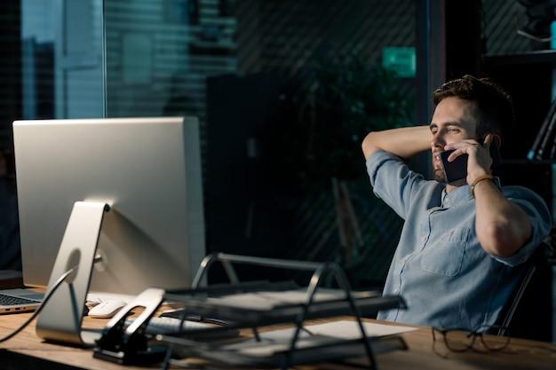 Uitgeput werknemer met telefoon in office