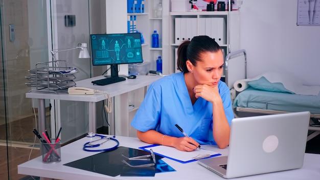 Uitgeputte assistent die naar het laptopscherm staart, op het klembord wringt, werkt vanuit het ziekenhuiskantoor. arts in de geneeskunde uniforme schrijflijst van geraadpleegde, gediagnosticeerde patiënten, die onderzoek doen.