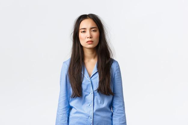 Uitgeputte aziatische vrouw met rommelig haar nadat ze in bed lag, pyjama droeg, er moe uitzag met slaperige ogen omdat ze aan slapeloosheid leed, niet veel geslapen had, vroeg wakker werd, witte achtergrond stond