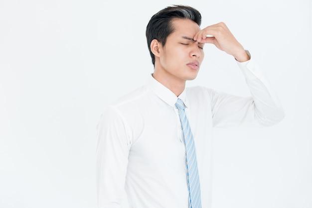 Uitgeputte aziatische zakenman die pijn voelt
