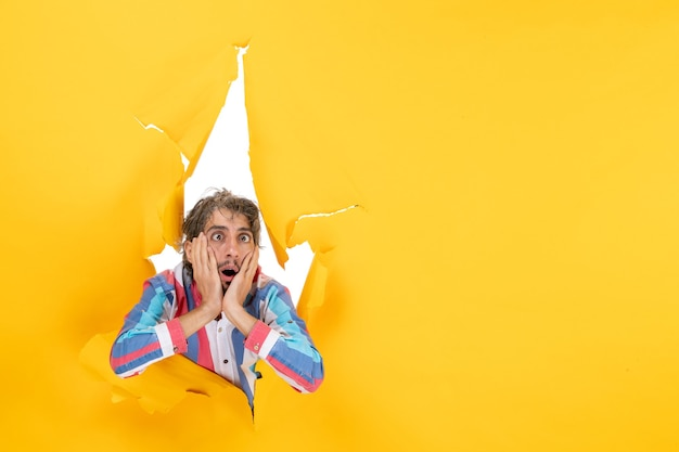 Uitgeputte en emotionele jongeman poseert op een gescheurde gele papieren gatenachtergrond