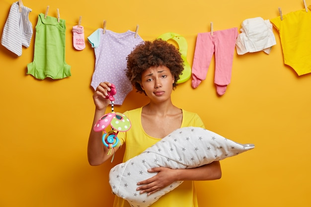 Uitgeputte etnische moeder brengt kostbare tijd door met pasgeboren baby, houdt mobiel vast, ziet er vermoeid uit, is moe van slapeloze nachten en zuigt borstvoeding. scène van bescherming en liefde. moederschap concept Gratis Foto