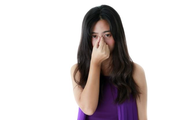 Uitgeputte etnische vrouw die de neus aanraakt en lijdt aan migraine terwijl ze naar de camera kijkt op een witte achtergrond.