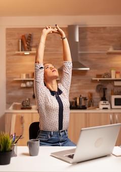 Uitgeputte freelancer-vrouw die zich uitstrekt terwijl ze 's avonds laat aan een deadline werkt. werknemer die om middernacht moderne technologie gebruikt en overuren maakt voor werk, zaken, drukte, carrière, netwerk, levensstijl, draadloos