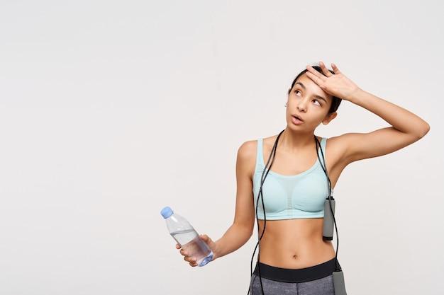 Uitgeputte jonge bruinharige vrouw met paardenstaartkapsel die het zweet met opgeheven hand afveegt na een harde training, water vasthouden terwijl ze poseren over witte muur