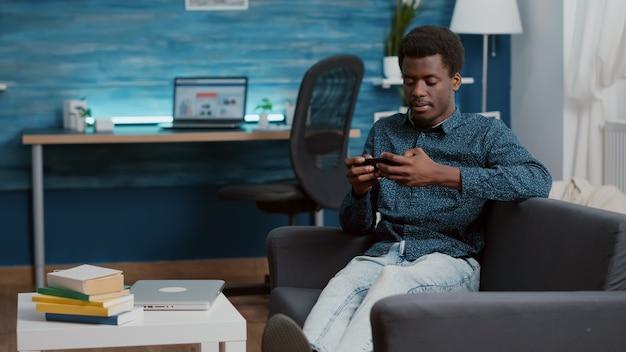 Uitgeputte jonge man die in slaap valt terwijl hij de telefoon in zijn handen houdt