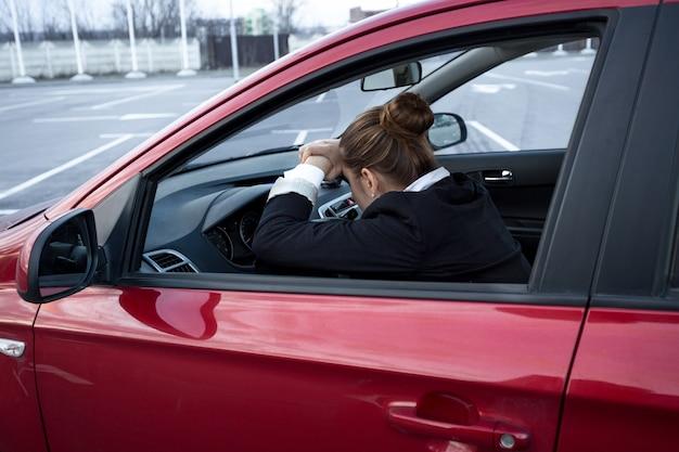 Uitgeputte jonge vrouw die slaapt tijdens het autorijden