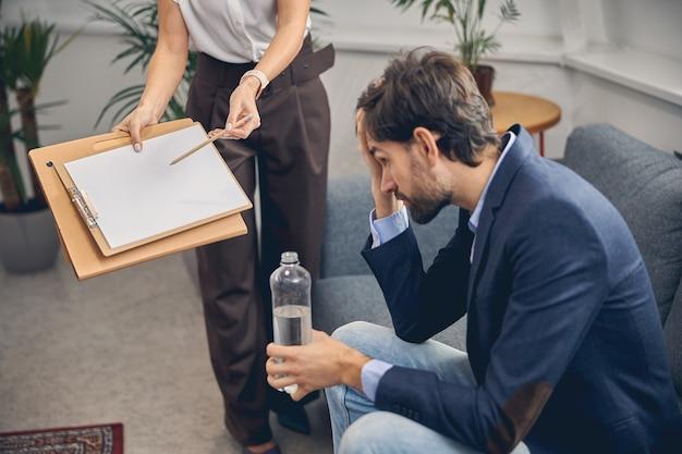 Uitgeputte jongeman die migraine heeft en een fles water vasthoudt terwijl zijn vrouwelijke collega naar het klembord wijst