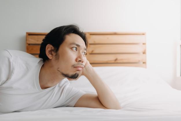Uitgeputte man lag op bed terwijl hij een burn-out voelde