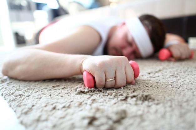 Uitgeputte man slapen en halters in handen houden
