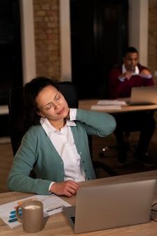 Uitgeputte mensen op kantoor die laat aan het werk zijn