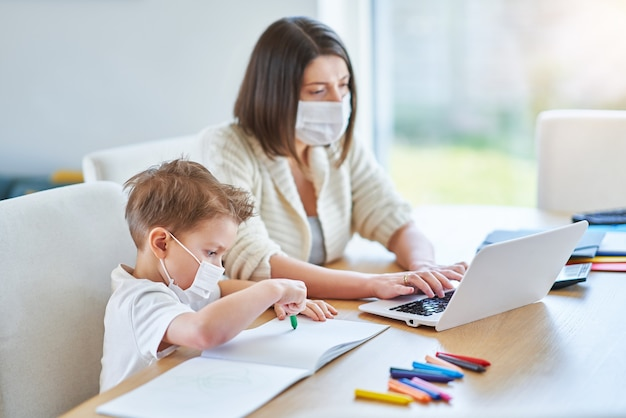 Uitgeputte moeder die thuis probeert te werken en voor haar zoon zorgt tijdens de pandemie van het coronavirus