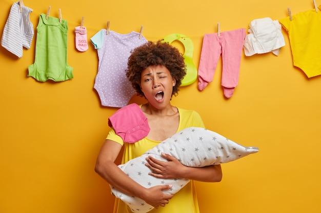 Uitgeputte moeder gaapt en wil slapen, poseert met pasgeboren baby gewikkeld in een deken, moe van huishoudelijke klusjes, heeft veel werk als geeft om de baby. ouderschap, vermoeidheid en moederschap