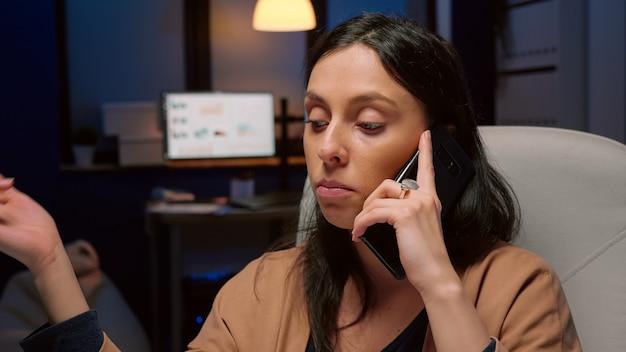 Uitgeputte ondernemer die managementgrafieken bespreekt die gebaren maken tijdens onderhandelingen, telefoongesprek dat 's avonds laat in het kantoor van het bedrijf werkt