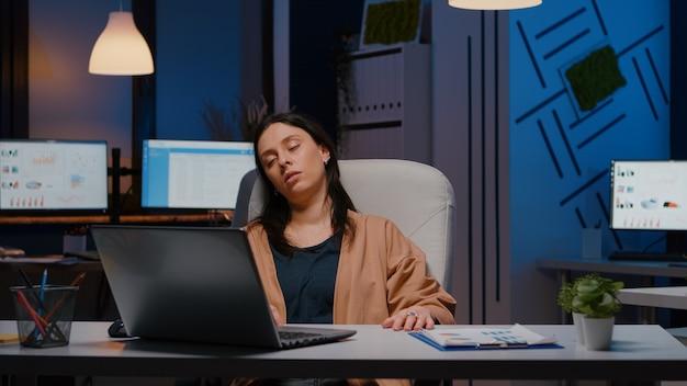 Uitgeputte ondernemersvrouw die voor laptop slaapt terwijl ze financiële statistieken analyseert