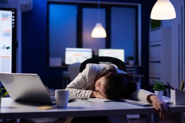 Uitgeputte overbelaste zakenvrouw die in slaap valt op een bureau met een opengeklapte laptop terwijl ze werkt aan een marketingproject in het startbureau van een bedrijf