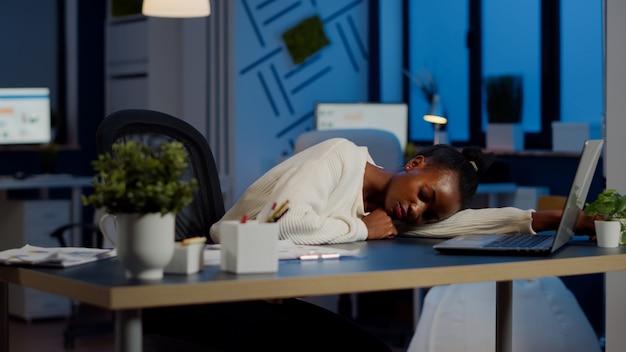 Uitgeputte overbelasting afrikaanse zakenvrouw die in slaap valt op een bureau met een opengeklapte laptopmonitor terwijl ze in een startbedrijf werkt. overwerkte werknemer die overuren maakt met inachtneming van de deadline, slapen