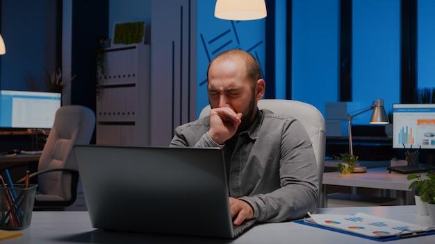 Uitgeputte slaperige zakenman die geeuwt terwijl hij aan de deadline van het managementproject werkt